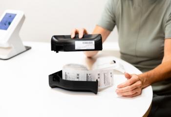 Apotheker Chantal demonstreert hoe de medicatierol in de cassette van een dispenser gaat.